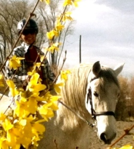 Photo of Cheri on her horse Monarch behind flowers